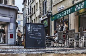 Lavagna con il menu della colazione si trova di fronte a una brasserie in Place du Change ad Avignone