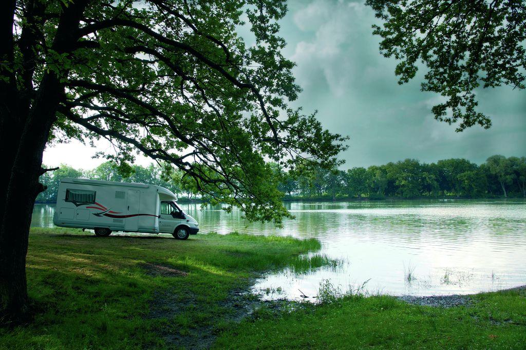 Un camper profilato in sosta in riva al lago